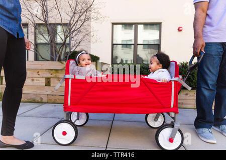 La section basse des parents par les filles debout assis en poussette sur sentier Banque D'Images