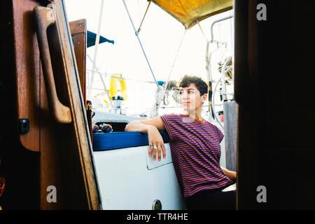 Thoughtful woman looking away while sitting in bateau contre ciel vu par la fenêtre