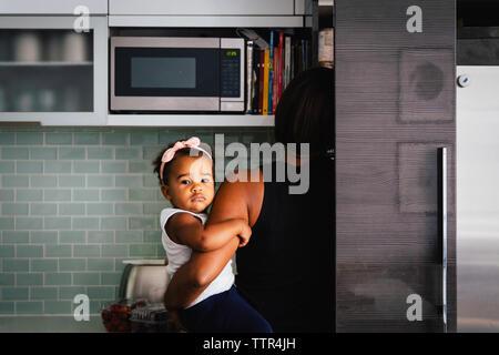 Vue arrière du mère portant mignon fille debout dans la cuisine à la maison Banque D'Images