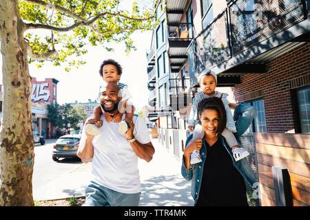 Portrait of happy parents transportant des enfants sur les épaules tout en marchant sur un trottoir en ville Banque D'Images