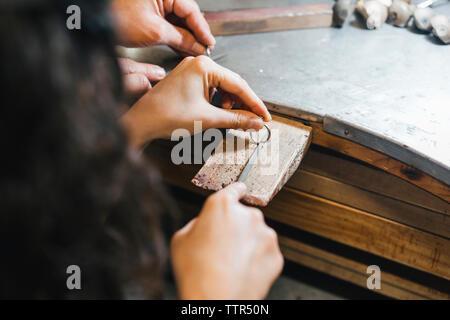 Les mains coupées de l'enseignement enseignant étudiant à faire sonner sur la table dans l'atelier