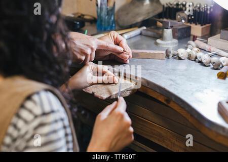 Les mains coupées de l'enseignement enseignant étudiant à l'anneau de forme sur la table à l'atelier