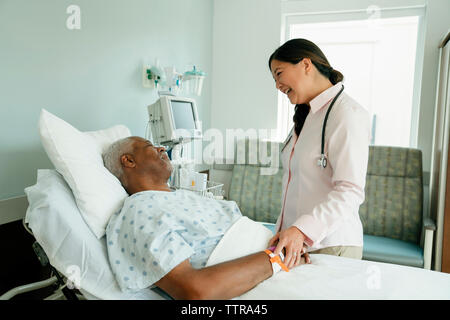 Cheerful doctor talking with senior patient lying on bed in hospital ward Banque D'Images