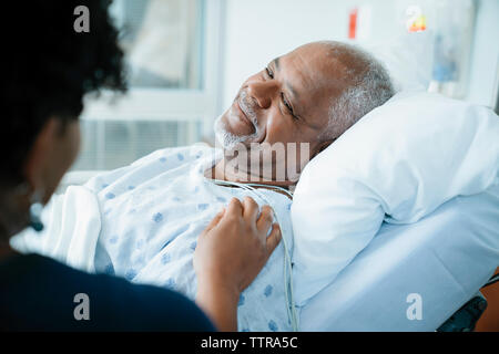 Portrait de fille toucher père lying on bed in hospital ward