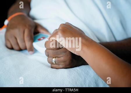 Fille de la main coupée tenant main du père in hospital ward Banque D'Images