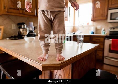 La section basse de garçon debout sur une table en bois dans la cuisine Banque D'Images
