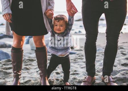 Les parents de la section basse du fils holding hands while standing on sand at beach Banque D'Images