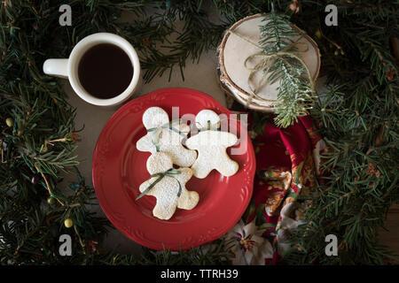 Vue aérienne d'hommes de pain d'épice avec du café noir et des brindilles durant les fêtes de Noël sur la table Banque D'Images