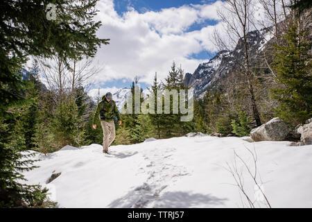 Randonneur marchant sur snowcapped mountain contre ciel nuageux