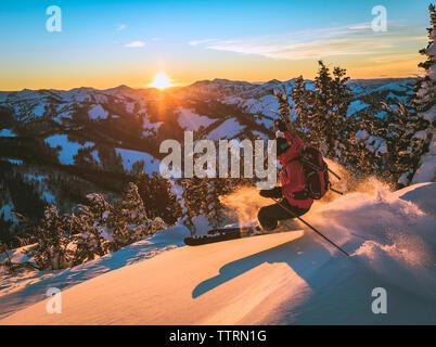 Ski femme sur pente de neige pendant le coucher du soleil