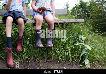 La section basse de la fratrie portant des bottes malpropres alors qu'assis sur un banc sur le terrain Banque D'Images