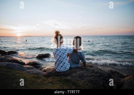 Vue arrière de la fratrie assis sur des roches par le lac Simcoe contre le ciel au coucher du soleil Banque D'Images