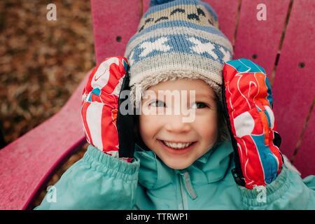 Portrait de jeune fille de 4 smiling avec chapeau, gants et enduire