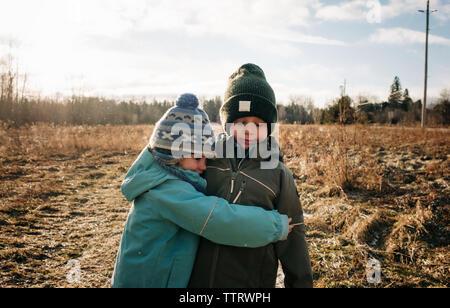 Frère et sœur hugging boy and girl câlins à l'extérieur jouer