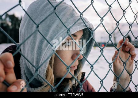 Portrait de femme avec son capot s'accrochant à une clôture métallique de penser