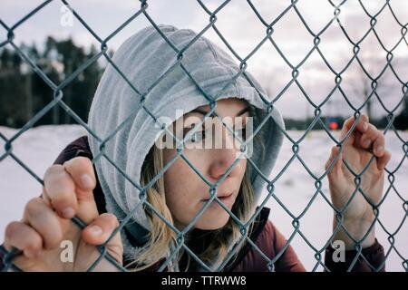 Portrait de femme tenant une clôture métallique en hiver avec capot
