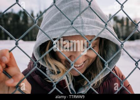 Portrait of woman smiling holding sur une clôture métallique avec capot