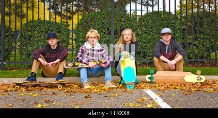 Portrait d'amis avec skateboards assis sur sentier au parc au cours de l'automne Banque D'Images