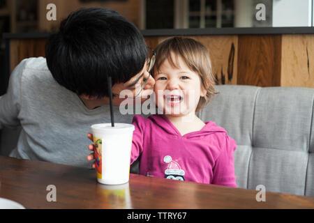 Les baisers heureux père fille, alors qu'assis à table dans cafe Banque D'Images