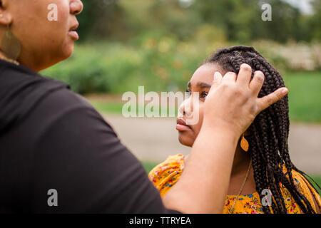 Au milieu de la mère avec la main dans les cheveux de sa fille au parc