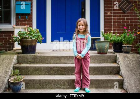 Portrait of a cute girl debout sur son front stoop Banque D'Images