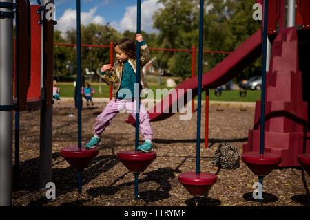 Une petite fille indépendante fière grimpe sur un jeu pour enfants Banque D'Images