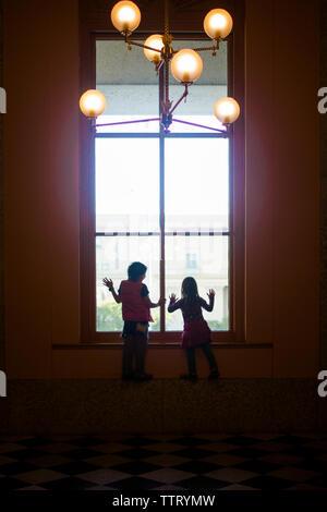 Silhouette de deux enfants à la recherche d'une grande fenêtre