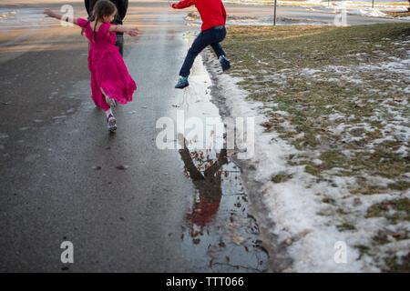 Deux enfants heureux leap et dance on marche dans la rue avec le père