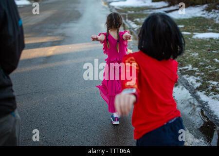 Deux petits enfants heureux mars vers le bas de la rue enneigée avec leur parent