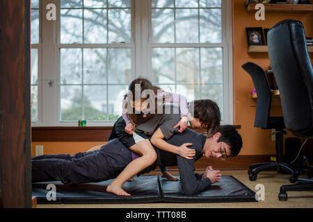 Un père tient une position de yoga avec deux enfants empilés sur son dos