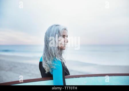 Vue côté femme réfléchie surfer carrying surfboard at Delray Beach Banque D'Images