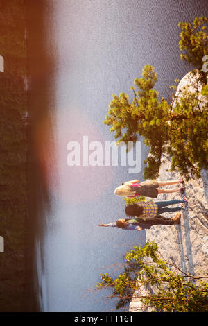 High angle view of friends standing on rock by lake Banque D'Images