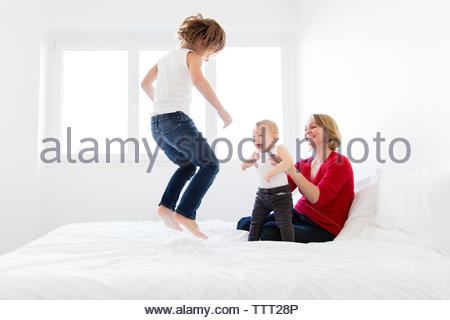 Happy mother and son looking at boy jumping on bed in home Banque D'Images