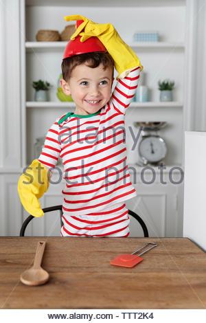 Dingo Garçon jouant avec ustensile de cuisine portant au milieu de la tête de l'entonnoir Banque D'Images