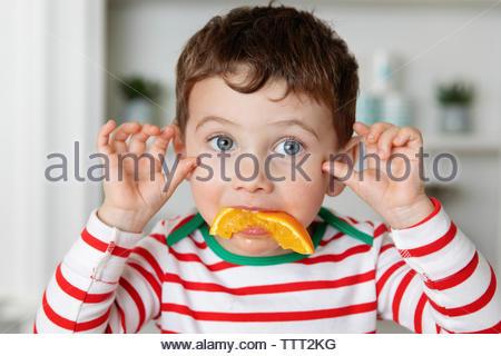 Little Boy making funny face avec tranche d'orange dans la bouche Banque D'Images