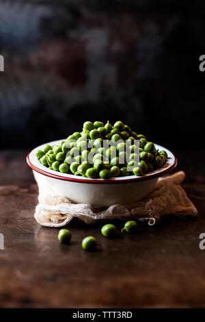 Petits pois dans un bol sur serviette à compteur de cuisine Banque D'Images