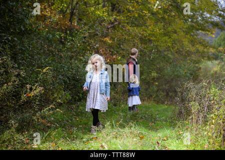 Petite fille qui marche loin de mon père et sa soeur en bois porte une robe Banque D'Images