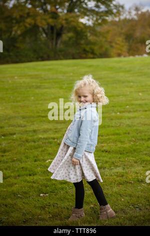 Toute la longueur de petite fille aux cheveux blonds smiling in field Banque D'Images