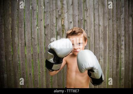Portrait of boy wearing boxing gloves at backyard Banque D'Images