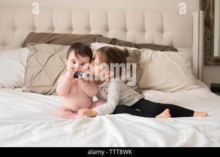 Soeur d'amour baisers frère torse nu assis sur le lit à la maison Banque D'Images