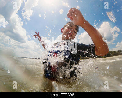 Low angle view of woman swimming in sea against cloudy sky Banque D'Images