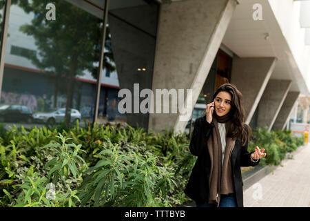 Femme d'affaires attrayant marcher dans la ville tout en utilisant son téléphone