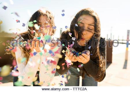 Deux filles blowing confetti de ses mains dans un vent à l'extérieur Banque D'Images