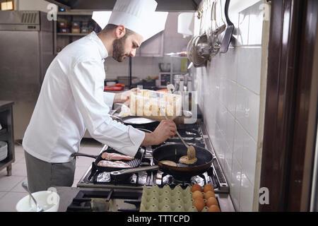 Vue latérale du chef la cuisson dans une poêle à crêpes sur cuisinière à cuisine commerciale Banque D'Images