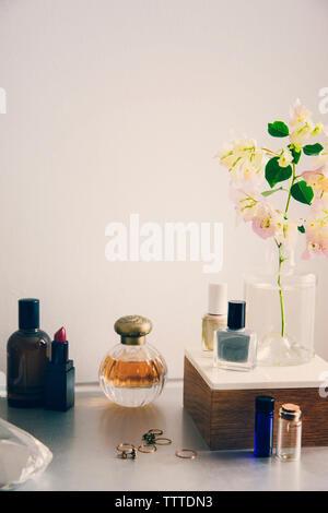 Produits de beauté avec des bijoux et vase à fleurs sur table contre mur blanc