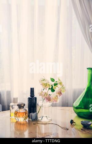 Produits de beauté avec des bijoux par vase à fleurs sur table rideau contre