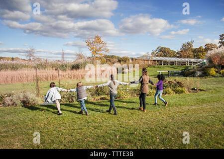 La lecture de l'enseignant avec les élèves sur les champs pendant le voyage Banque D'Images