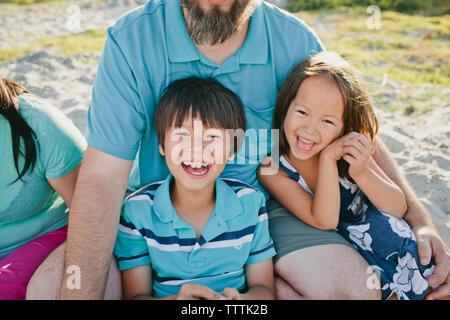 Portrait d'enfants heureux avec les parents at beach Banque D'Images