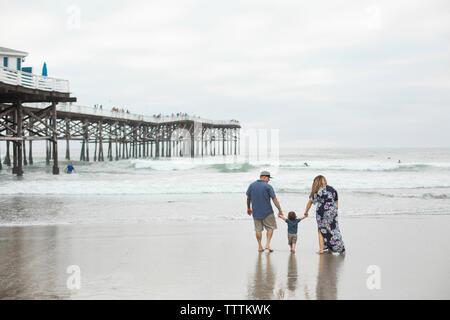 Vue arrière de son holding mains des parents tout en marchant vers la mer sur la plage de rive contre ciel à Banque D'Images