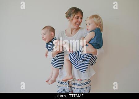 Mère joyeuse transportant des enfants contre fond blanc Banque D'Images
